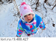 Маленький ребенок в синей теплой одежде смотрит вверх на фоне зимнего снежного пейзажа. Стоковое фото, фотограф Daniela / Фотобанк Лори