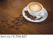 Купить «Cup of cappuccino with coffee art and coffee beans», фото № 9754427, снято 24 апреля 2015 г. (c) Wavebreak Media / Фотобанк Лори