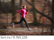 Купить «Young woman running outdoors in a forest», фото № 9765235, снято 16 декабря 2017 г. (c) PantherMedia / Фотобанк Лори