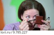 Купить «Симпатичная молодая женщина наносит тени на веки глаз, смотрит в зеркальце, движение камеры», видеоролик № 9785227, снято 22 июня 2015 г. (c) Кекяляйнен Андрей / Фотобанк Лори