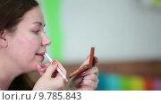 Купить «Женщина подкрашивает губы специальным карандашом для губ, смотрит в зеркальце», видеоролик № 9785843, снято 22 июня 2015 г. (c) Кекяляйнен Андрей / Фотобанк Лори