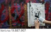 Купить «Художник наносит граффити с портретом Виктора Цоя на мемориальной стене на улице Арбат в центре города Москвы в 25-летний юбилей со дня гибели певца, Россия», видеоролик № 9887907, снято 16 августа 2015 г. (c) Николай Винокуров / Фотобанк Лори