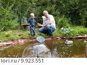 Купить «Дедушка с внуком у пруда на дачном участке», фото № 9923551, снято 15 августа 2015 г. (c) Светлана Чуйкова / Фотобанк Лори