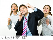 Купить «Portrait of three business partners holding their arms up and looking upwards with businessman speaking on the phone», фото № 9991927, снято 17 февраля 2020 г. (c) PantherMedia / Фотобанк Лори