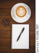 Купить «Cup of cappuccino with coffee art and notepad», фото № 10006787, снято 24 апреля 2015 г. (c) Wavebreak Media / Фотобанк Лори