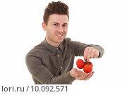 Купить «Young man smiling with tomatoes», фото № 10092571, снято 22 марта 2019 г. (c) PantherMedia / Фотобанк Лори