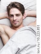 Красивый молодой мужчина лежит на постели. Стоковое фото, фотограф Дмитрий Булин / Фотобанк Лори