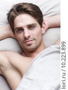 Купить «Красивый молодой мужчина лежит на постели», фото № 10223899, снято 9 июня 2015 г. (c) Дмитрий Булин / Фотобанк Лори