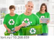 Smiling eco-minded man holding recycling box. Стоковое фото, агентство Wavebreak Media / Фотобанк Лори