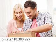 Купить «happy couple with parcel box at home», фото № 10300927, снято 6 июня 2015 г. (c) Syda Productions / Фотобанк Лори