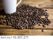 Купить «Coffee beans on a table with cup», фото № 10307271, снято 16 апреля 2015 г. (c) Wavebreak Media / Фотобанк Лори