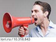 Молодой мужчина кричит в мегафон на сером фоне. Стоковое фото, фотограф Дмитрий Булин / Фотобанк Лори