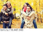 Купить «smiling friends having fun in autumn park», фото № 10447343, снято 4 октября 2014 г. (c) Syda Productions / Фотобанк Лори