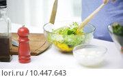 Купить «smiling woman cooking vegetable salad at home», видеоролик № 10447643, снято 2 мая 2015 г. (c) Syda Productions / Фотобанк Лори