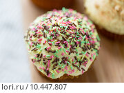 Купить «close up of glazed cupcake or muffin on table», фото № 10447807, снято 21 мая 2015 г. (c) Syda Productions / Фотобанк Лори