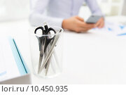 Купить «close up of cup with scissors and pens at office», фото № 10450935, снято 18 июня 2015 г. (c) Syda Productions / Фотобанк Лори