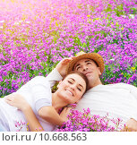 Купить «Young family on floral glade», фото № 10668563, снято 18 июня 2019 г. (c) PantherMedia / Фотобанк Лори