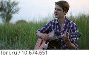 Купить «Молодой парень играет на гитаре», видеоролик № 10674651, снято 1 августа 2015 г. (c) Алексндр Сидоренко / Фотобанк Лори