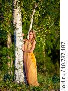 Купить «Молодая девушка в желтом платье стоит у берёзы», фото № 10787187, снято 16 августа 2015 г. (c) Литвяк Игорь / Фотобанк Лори