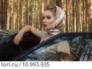 Купить «Девушка в ретростиле стоит у автомобиля в летнем лесу», фото № 10993935, снято 15 июня 2015 г. (c) Дмитрий Черевко / Фотобанк Лори