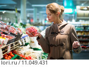 Купить «Pretty, young woman shopping for fruits and vegetables in produce department of a grocery store/supermarket», фото № 11049431, снято 13 декабря 2017 г. (c) PantherMedia / Фотобанк Лори
