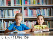 Купить «Portrait of cheerful schoolchildren looking at camera while sitting in library», фото № 11098159, снято 17 января 2020 г. (c) PantherMedia / Фотобанк Лори