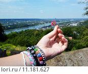 Цветок в женской руке с браслетами на фоне пейзажа. Стоковое фото, фотограф Наталья Буравлева / Фотобанк Лори