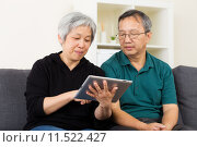 Asian old couple using tablet. Стоковое фото, фотограф Leung Cho Pan / PantherMedia / Фотобанк Лори