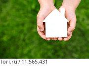 Купить «Недвижимость, домик в руках на зеленом фоне», фото № 11565431, снято 22 июня 2015 г. (c) Захар Гончаров / Фотобанк Лори
