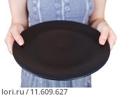 Купить «woman holds empty black plate», фото № 11609627, снято 20 июня 2019 г. (c) PantherMedia / Фотобанк Лори