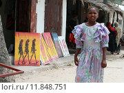 Занзибар, Танзания, африканская девочка, приблизительно десяти лет, стоит на фоне, выставленных на продажу картин местных художников в сувенирной лавке (2008 год). Редакционное фото, фотограф Владимир Григорьев / Фотобанк Лори