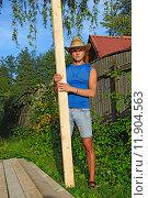 Купить «Молодой мужчина с сосновой доской в руках около штабеля досок на приусадебном участке летом в солнечный день», фото № 11904563, снято 5 августа 2015 г. (c) Максим Мицун / Фотобанк Лори