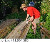 Купить «Молодой мужчина в соломенной шляпе укладывает доски в штабель летом в солнечный день в деревне крупным планом», фото № 11904583, снято 5 августа 2015 г. (c) Максим Мицун / Фотобанк Лори