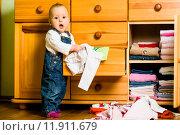 Купить «Domestic chores - baby throws out clothes», фото № 11911679, снято 29 января 2020 г. (c) PantherMedia / Фотобанк Лори