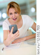 Купить «Woman in office looking at smartphone with scary look », фото № 12032703, снято 30 октября 2018 г. (c) PantherMedia / Фотобанк Лори