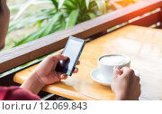 Купить «man drink coffee and use smart phone in coffee shop at evening», фото № 12069843, снято 24 января 2019 г. (c) PantherMedia / Фотобанк Лори