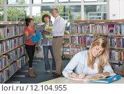Купить «Teacher and students studying in school library», фото № 12104955, снято 22 апреля 2018 г. (c) PantherMedia / Фотобанк Лори