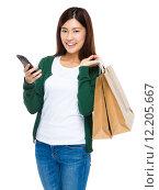 Купить «Woman with shopping bag and holding mobile phone», фото № 12205667, снято 26 апреля 2019 г. (c) PantherMedia / Фотобанк Лори