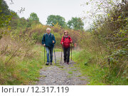 Купить «Senior couple Nordic walking on the trail in nature», фото № 12317119, снято 21 августа 2019 г. (c) PantherMedia / Фотобанк Лори