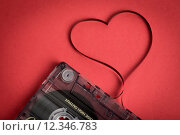 Купить «Audio cassette tape on red backgound. Film shaping heart», фото № 12346783, снято 20 марта 2019 г. (c) PantherMedia / Фотобанк Лори