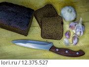 Чеснок, черный хлеб и нож. Стоковое фото, фотограф Евгений Чернышов / Фотобанк Лори