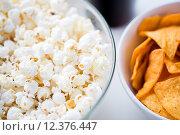 Купить «close up of popcorn and corn crisps or nachos», фото № 12376447, снято 21 мая 2015 г. (c) Syda Productions / Фотобанк Лори