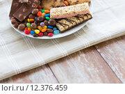 Купить «close up of candies, chocolate, muesli and cookies», фото № 12376459, снято 22 мая 2015 г. (c) Syda Productions / Фотобанк Лори