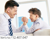 Купить «Young man and his son armwrestling», фото № 12407047, снято 25 июня 2019 г. (c) PantherMedia / Фотобанк Лори