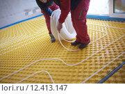 Купить «workers installing underfloor heating system», фото № 12413147, снято 21 марта 2019 г. (c) PantherMedia / Фотобанк Лори