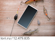 Купить «Fishing equipment with a cellphone on a wooden background», фото № 12479835, снято 23 мая 2018 г. (c) PantherMedia / Фотобанк Лори