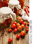 Купить «Свежие помидоры и маринованные помидоры в банках на столе», фото № 12588143, снято 1 сентября 2015 г. (c) Надежда Мишкова / Фотобанк Лори