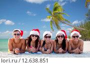 Купить «group of friends in santa helper hats on beach», фото № 12638851, снято 3 августа 2014 г. (c) Syda Productions / Фотобанк Лори