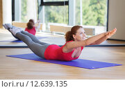 Купить «smiling woman doing exercise on mat in gym», фото № 12639135, снято 7 июня 2014 г. (c) Syda Productions / Фотобанк Лори