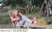 Молодая активная женщина общается по телефону в сельской местности на природе сидя на шезлонге. Стоковое видео, видеограф Земсков Андрей  Владимирович / Фотобанк Лори